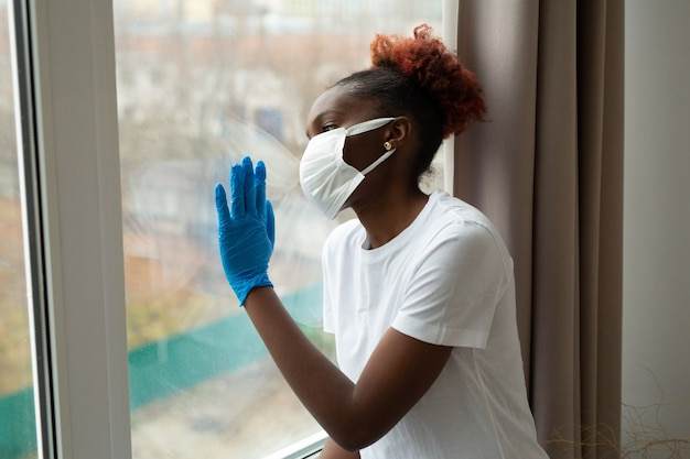 Young african woman in medical mask near the window