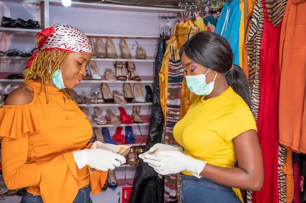 현금으로 지불하는 지역 상점에서 지불하는 젊은 아프리카 여성