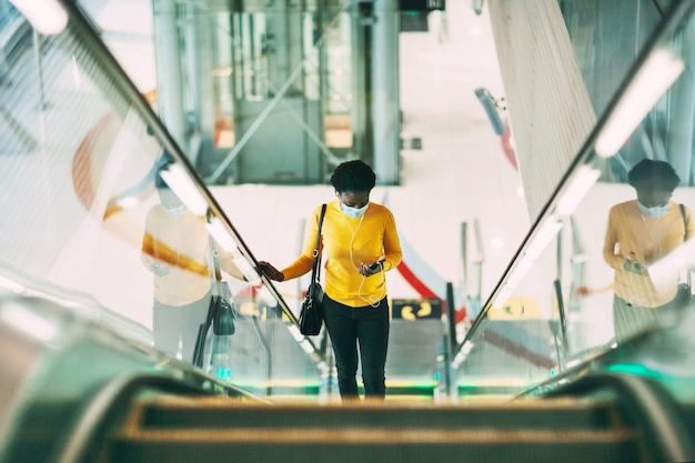 A young african woman in a protective medical mask climbs the escalator in the subway and listens to music with headphones. modern technologies, pandemic, social distance.