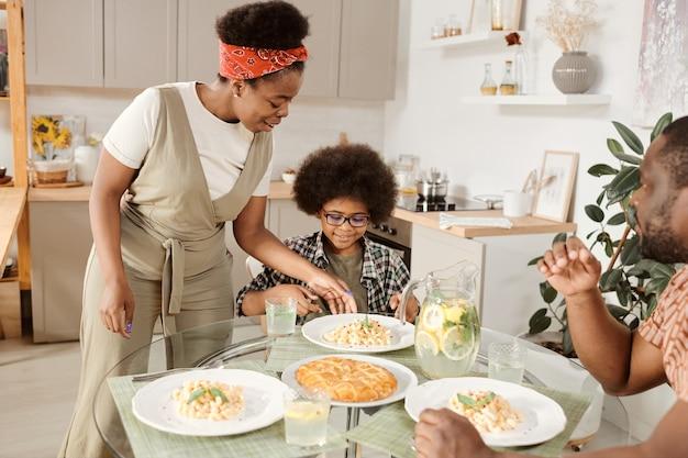 Молодая африканская женщина кладет тарелку с пастой на сервированный стол ее маленьким сыном