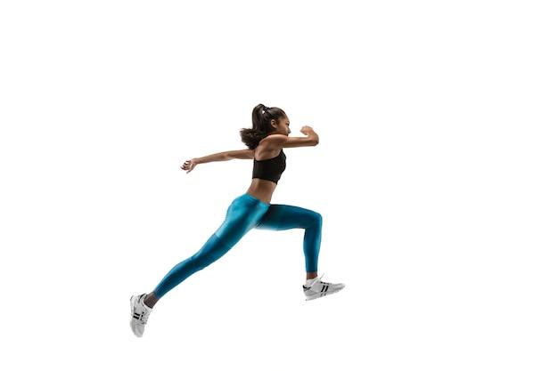 白いスタジオの背景に孤立して実行している若いアフリカの女性。 1人の女性ランナーまたはジョガー。ジョギングアスリートのシルエット