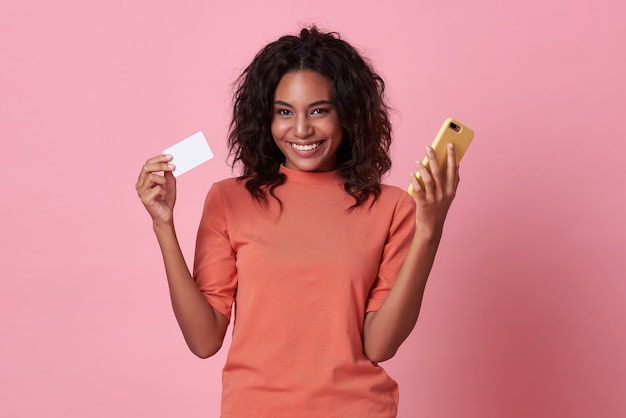 Young african woman showing a credit card and mobile phone on pink background