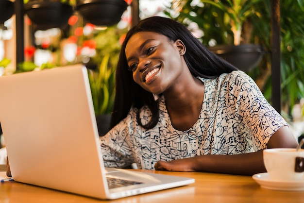 ノートパソコンに取り組んでいるカフェに座っている若いアフリカの女性
