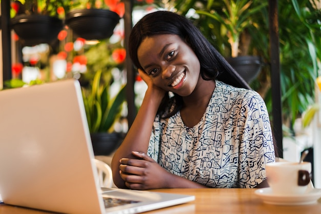 Young african woman siting at cafe working on laptop