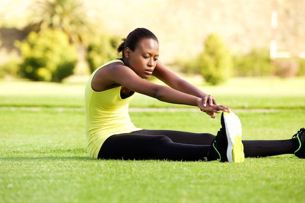 Young african woman sitting on grass stretching to reach toes