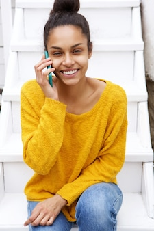 Young african woman sitting on staircase and making phone call