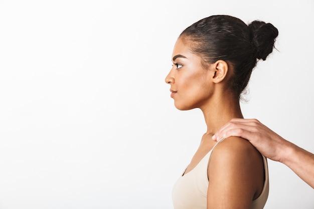남자의 손을 흰색에 고립 된 그녀의 어깨를 잡고 앉아 젊은 아프리카 여자