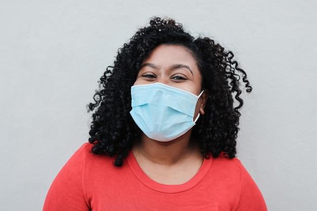 安全マスクを着用しながらカメラに笑みを浮かべて若いアフリカの女性-顔に焦点を当てる Premium写真