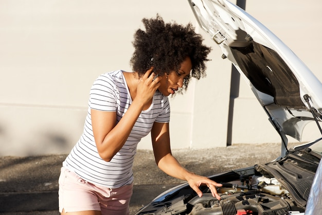 Young african woman standing by broken down car parked on the road and calling for assistance