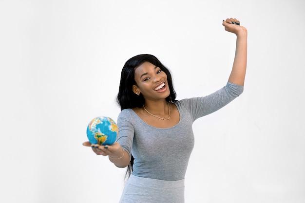 Молодое африканское положение женщины изолированное на белой стене держа глобус земли litlle