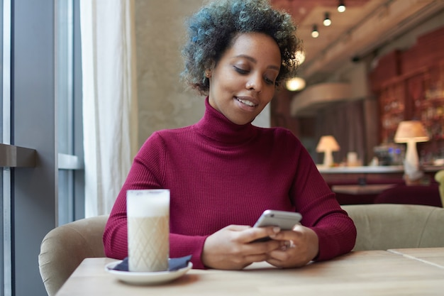 Young african woman surfing internet or using dating app with her phone in cozy cafe