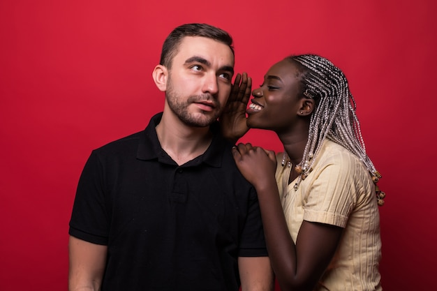Young african woman telling a secret to a man over a red background
