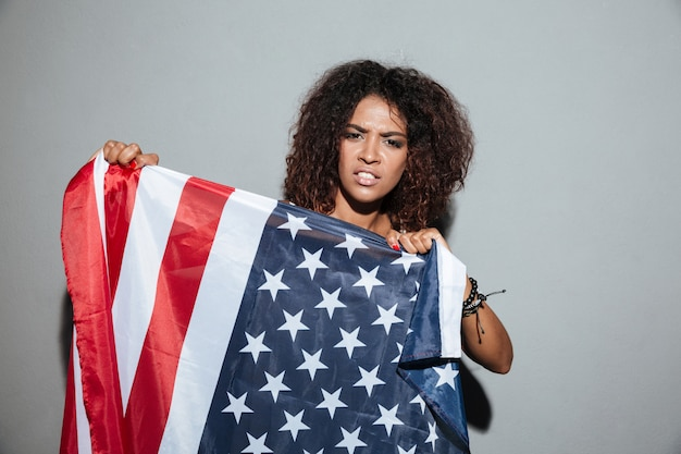 Young african woman trying to tear apart usa flag