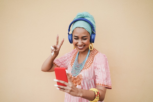 Young african woman using mobile phone app for creating playlist music