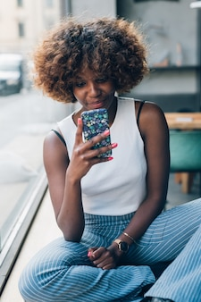 Young african woman using smartphone and relaxing