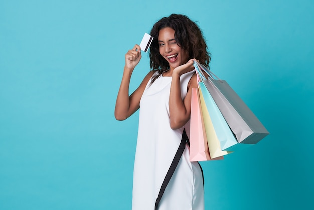 Young african woman in white dress holding shopping bags and credit card