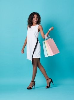 Young african woman in white dress holding shopping bags