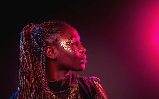 Young african woman with afro hairstyle and golden shiny makeup. studio shot. blue and pink neon light flare.