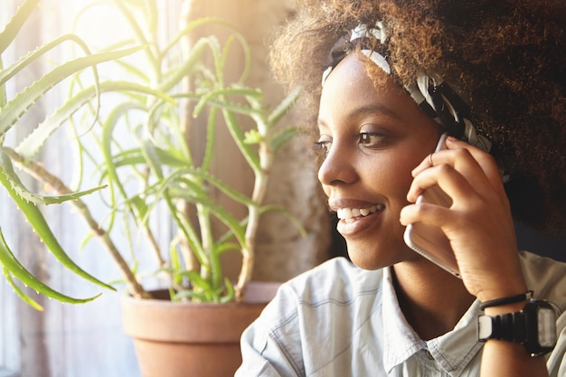 電話で話している巻き毛を持つ若いアフリカ人女性