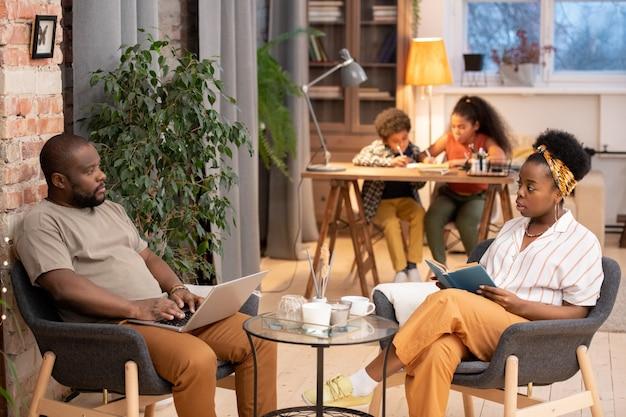 책을 펼친 젊은 아프리카 여성과 아이들이 숙제를 하는 동안 작은 탁자 옆에 회색 안락의자에 앉아 노트북을 들고 있는 남편