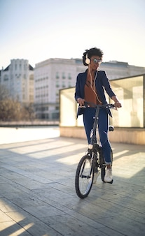 音楽を聴きながら屋外で自転車に乗る短い巻き毛の若いアフリカの女性