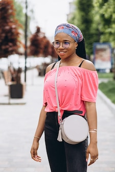Young african woman with stylish bag wearing glasses outdoors.
