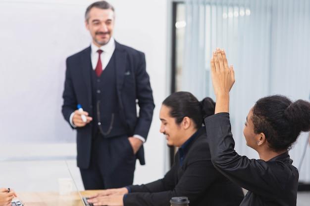 젊은 아프리카 여성들은 비즈니스 회의실에서 그녀의 상사에게 질문하기 위해 손을 들었다