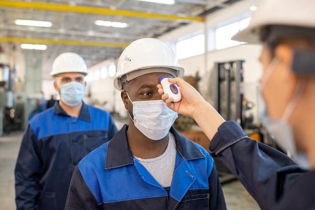 同僚が持っている電子体温計で体温を測定している作業服と保護マスクの若いアフリカ人労働者