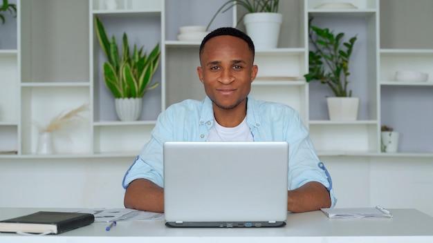 영 아프리카 계 미국인 홈 오피스 미소에 앉아있다. 만족 된 젊은 남자의 초상화는 집에서 자신의 노트북에서 일하고 있습니다