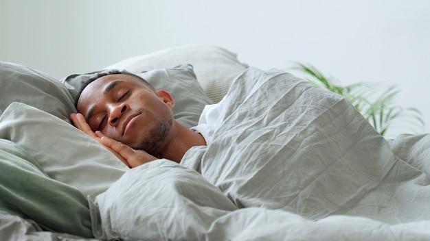 Афро-американский мужчина спит в постели у себя дома