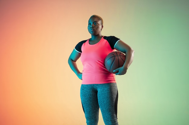 Young africanamerican plus size female models training on gradient wall