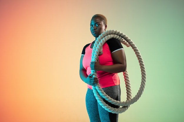 Giovani modelli femminili afroamericani plus size che si allenano sulla parete sfumata