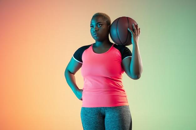 若いアフリカ系アメリカ人のプラスサイズの女性モデルが勾配壁でトレーニング