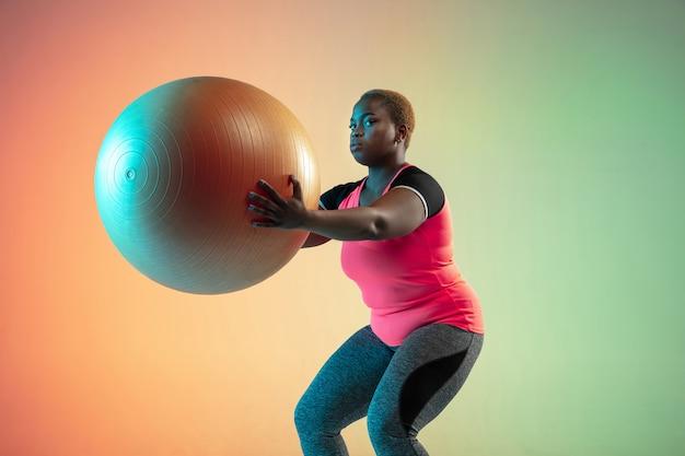 Молодые афроамериканские модели больших размеров тренируются на градиентной стене