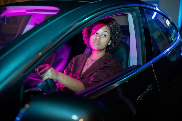 Young africanamerican woman driving electric car