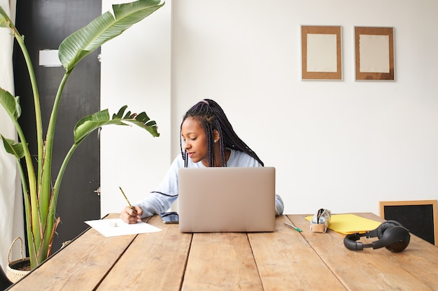 A young africanamerican woman works alone she is using a laptop and also taking notes in a notebook ...