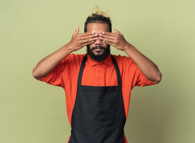 Giovane barbiere afroamericano che indossa l'uniforme che copre gli occhi con le mani