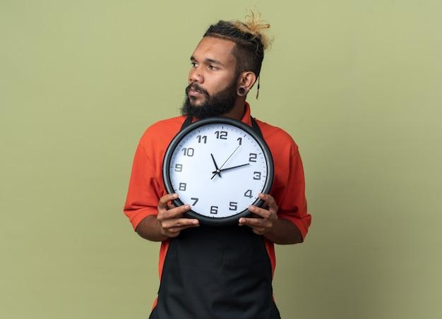 Giovane barbiere afroamericano che indossa l'uniforme che tiene l'orologio guardando a lato