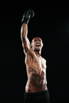 若いアフロアメリカンボクサーが黒い手袋で上げられた腕で彼の勝利を祝う