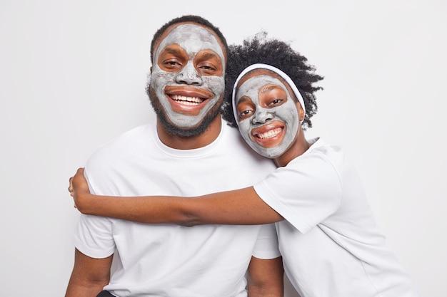 Il giovane ragazzo e la ragazza afroamericani si abbracciano con amore hanno buoni rapporti applicano maschere di argilla sul viso per ringiovanire il sorriso della pelle felicemente isolato sul muro bianco