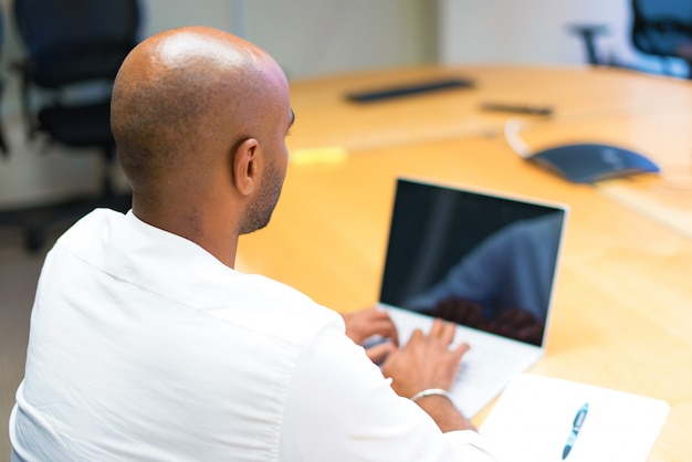 Young afro american businessman in the office with his laptop in back position