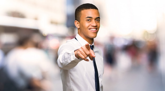 Young afro american businessman points finger at you with a confident expression in the city
