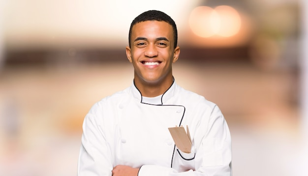 Young afro american chef man happy and smiling on unfocused wall
