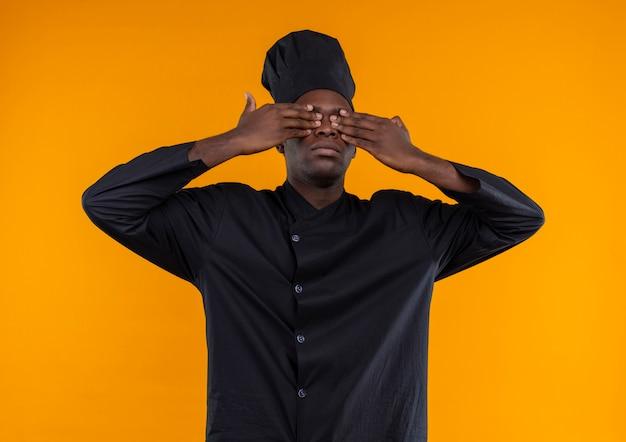 Il giovane cuoco afroamericano in uniforme del cuoco unico chiude gli occhi con le mani isolate sullo spazio arancione con lo spazio della copia