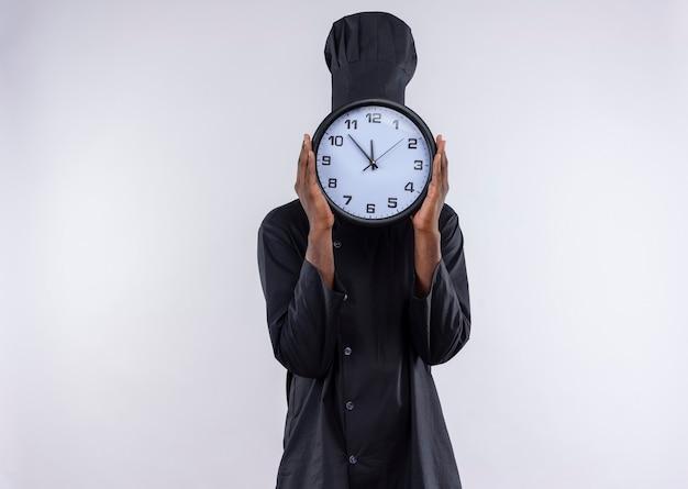 Il giovane cuoco afroamericano in uniforme del cuoco unico chiude il fronte con l'orologio su bianco con lo spazio della copia