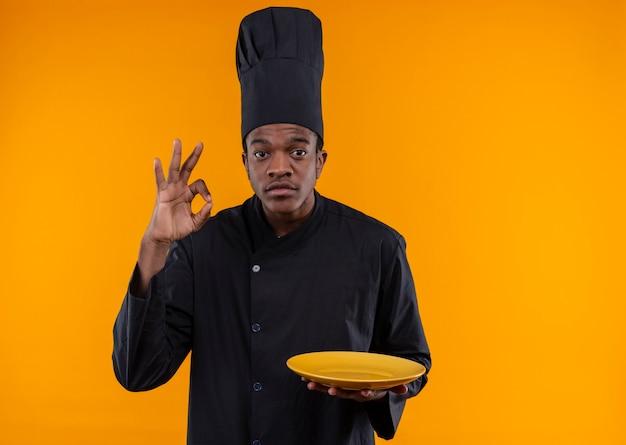 シェフの制服のジェスチャーで若いアフリカ系アメリカ人の料理人は、手のサインをokし、コピースペースでオレンジ色の背景に分離されたプレートを保持します