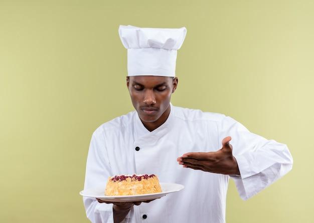 シェフの制服を着た若いアフリカ系アメリカ人の料理人は、プレートにケーキを保持し、コピースペースで緑の背景に分離された手でポイント