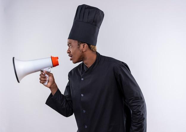 シェフの制服を着た若いアフリカ系アメリカ人の料理人は、スピーカーを保持し、コピースペースで白い背景で隔離された側に見えます