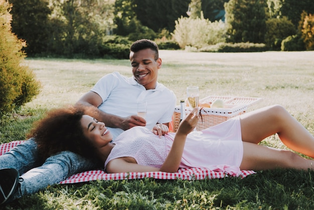 Young afro-american couple in love is resting in park