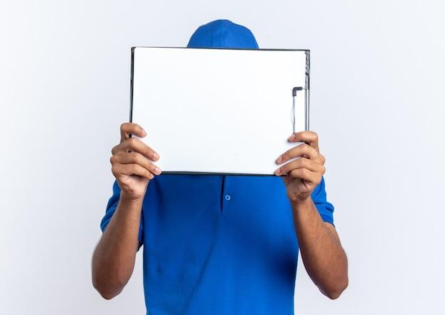 Молодой афро-американский курьер, держащий буфер обмена перед его лицом, изолированным на белом фоне с копией пространства